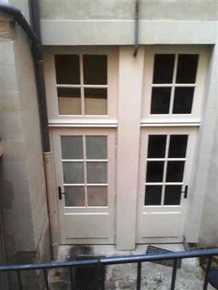 Vue d'une cour intérieure dans une copropriété après travaux (fabrication des ouvertures en chêne en nos ateliers) en secteur sauvegardé dans le centre de Nantes
