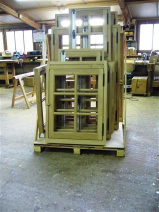 Série d'ouvertures en chêne à mouton et gueule de loup en simple et double vitrage en sortie de fabrication ,avant peinture d'impression.